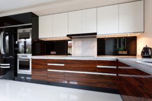 Białe szafki, czarne kafelki i drewniane blaty tworzą piękny gradient