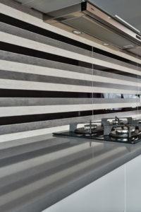 Blat kuchenny z płytą gazową na tle szarych kafelków na ścianie