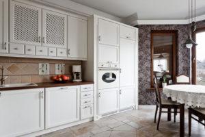 Białe meble i stylowa tapeta w kuchni